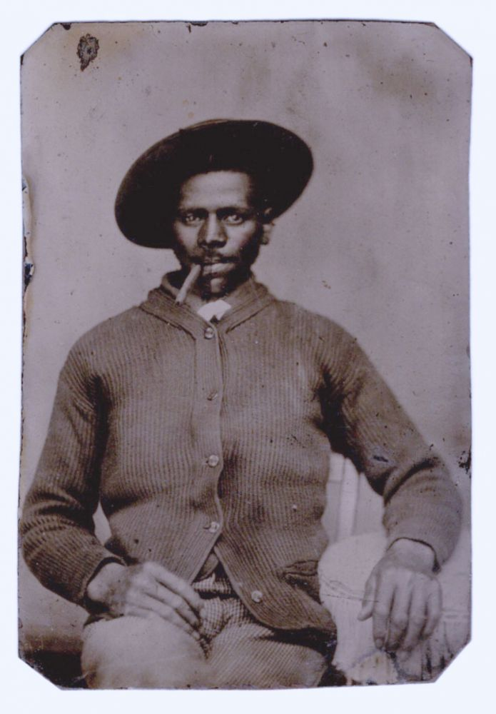 [Tintype portrait of an African American man smoking a cigar].